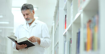 Doctor reading book in medical library